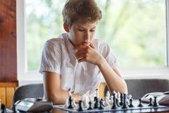 Śliczna, mądrze, młoda chłopiec w białej koszula, bawić się szachy na chessboard w sali lekcyjnej Edukacja, hobby, trenuje zdjęcia stock