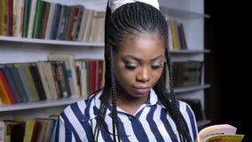 Śliczna młoda afrykańska dziewczyny czytelniczej książki pozycja i patrzeć kamerę z ładnym uśmiechem salowym