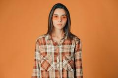 Śliczna młoda brunetki dziewczyna pokazuje nieufność na pomarańczowym tle zdjęcie stock