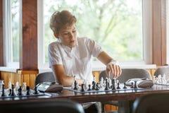 Śliczna, młoda chłopiec, bawić się szachy z drewnianym chessboard Szachowy turniej, lekcja, obóz, trenuje zdjęcia stock