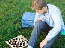 Śliczna młoda chłopiec w błękitnej koszula bawić się szachy na trawie w parku, plenerowym Hobby, edukacja zdjęcie stock