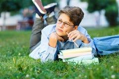 Śliczna, młoda chłopiec w round szkłach, i błękitna koszula piszemy z jego lewą ręką na trawie w parku podczas gdy kłamający eduk fotografia royalty free