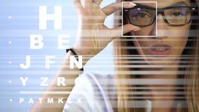 Śliczna młoda dorosła brunetki kobieta w szkłach przy kliniką sprawdza jej wzrok zbiory wideo