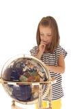 Śliczna młoda dziewczyna patrzeje światową kulę ziemską z palcem Zdjęcia Royalty Free