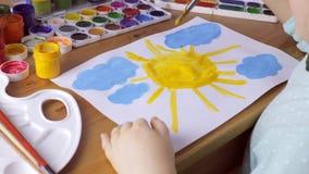 Śliczna młoda dziewczyna rysuje żółtego słońce i błękit chmurnieje tła błękitny pojęcia drabinowej pobliski ładnej farby obrazu p zbiory