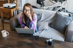 Śliczna młoda dziewczyna siedzi przy, ono uśmiecha się skromnie i komputerem z szkłami i spojrzeniami przy kamerą komputerowa ilu Zdjęcia Stock