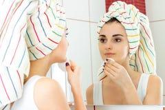 Śliczna młoda dziewczyna z ręcznikiem na włosów spojrzeniach w pocieraniach i lustrze twój twarz z bawełnianym dyskiem Zdjęcie Stock