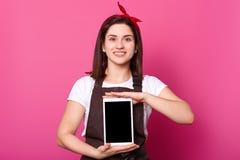 Śliczna młoda gospodyni stoi uśmiecha się jest ubranym t koszula, fartuch, czerwonego włosianego zespołu na głowie, spojrzenia pr zdjęcie stock