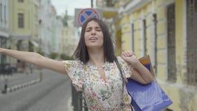 Śliczna młoda kobieta jest ubranym lato suknię z torbami na zakupy w rękach próbuje łapać taxi w ulicie stary zbiory