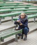 Śliczna młoda kobieta kuca w wiosny miasta parku outdoors z fachową dslr kamerą bierze obrazki Zdjęcie Stock