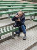 Śliczna młoda kobieta kuca w wiosny miasta parku outdoors z fachową dslr kamerą bierze obrazki Fotografia Stock
