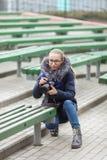 Śliczna młoda kobieta kuca w wiosny miasta parku outdoors z fachową dslr kamerą bierze obrazki Obrazy Stock