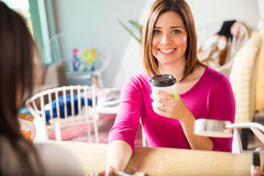 Śliczna młoda kobieta pije herbaty przy gwoździa salonem obrazy stock