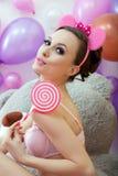 Śliczna młoda kobieta pozuje z różowym lizakiem Zdjęcia Royalty Free