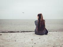 Śliczna młoda kobieta siedzi na piasku na plaży i patrzeje out w odległość Zdjęcie Royalty Free
