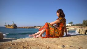 Śliczna młoda kobieta siedzi skalistym brzeg na tle malowniczy widok stary w lato sukni, okularach przeciwsłonecznych i zbiory