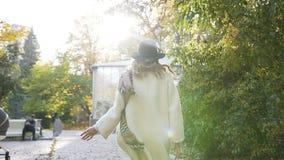 Śliczna młoda kobieta w białym żakiecie ma zabawę w parku podczas gdy chodzący zdjęcie wideo