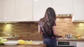 Śliczna młoda kobieta w czarnej koszulce gotuje w kuchni Jest śpiewająca i tancząca podczas gdy stewing niektóre zdrowych zbiory wideo