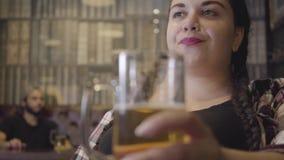 Śliczna młoda tłuściuchna kobieta siedzi przy z pigtails zakazuje kontuar z szkłem piwo podczas gdy dwa mężczyzn opowiadać zbiory wideo
