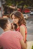 Śliczna młoda uśmiechnięta para siedzi outdoors przy zieloną miasto ulicą w miłości śmia się, ściskający, patrzeje each inny, lat Zdjęcia Stock