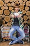 Śliczna młoda z włosami dziewczyna i mienie zabawkarski baranek na nieociosanej ławce siedzimy Drewniany tło Uprawiać ziemię poję fotografia royalty free