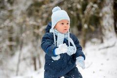 Śliczna mała berbeć chłopiec, bawić się outdoors z śniegiem na zima dniu obraz royalty free