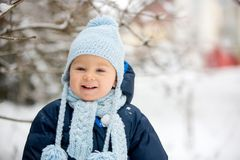 Śliczna mała berbeć chłopiec, bawić się outdoors z śniegiem na zima dniu obrazy royalty free