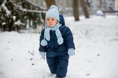 Śliczna mała berbeć chłopiec, bawić się outdoors z śniegiem na zima dniu zdjęcie stock