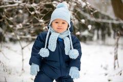 Śliczna mała berbeć chłopiec, bawić się outdoors z śniegiem na zima dniu obraz stock