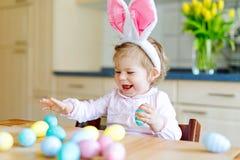 Śliczna mała berbeć dziewczyna jest ubranym Wielkanocnego królika ucho bawić się z barwionymi pastelowymi jajkami Szczęśliwi dzie zdjęcia stock