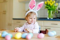 Śliczna mała berbeć dziewczyna jest ubranym Wielkanocnego królika ucho bawić się z barwionymi pastelowymi jajkami Szczęśliwi dzie zdjęcie stock