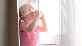 Śliczna mała blond dziewczyna pije jej ranek herbaty lub kawę okno w różowych okularach przeciwsłonecznych, patrzeje outsid zdjęcie wideo