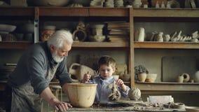 Śliczna mała chłopiec bawić się z gliną robi ceramicznej zabawce w jego dziadek ` s warsztacie Siwowłosy brodaty mężczyzna jest p zbiory wideo