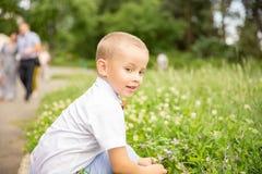 Śliczna mała chłopiec siedzi w trawie zdjęcia royalty free