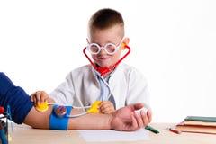 Śliczna mała doktorska chłopiec z uśmiechem na twarzy obsiadaniu przy jego biurkiem dalej fotografia stock