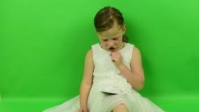 Śliczna mała dziewczyna czyta ebook na chroma klucza tle Mała dziewczynka ubierająca w romantycznej sukni white ślubny sukienkę zbiory wideo