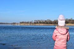 Śliczna mała dziewczynka bawić się blisko jeziora w jesień parku fotografia stock