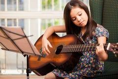 Śliczna mała dziewczynka bawić się gitarę Zdjęcia Royalty Free