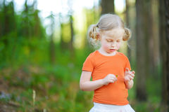 Śliczna mała dziewczynka bawić się ` kocha ja? kocha ja nie? ` stokrotki płatka gra Zdjęcie Stock