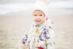 Śliczna mała dziewczynka bawić się na piaskowatej plaży Szczęśliwy dziecka być ubranym zdjęcia stock