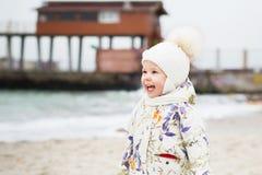 Śliczna mała dziewczynka bawić się na piaskowatej plaży Szczęśliwy dziecka być ubranym fotografia stock