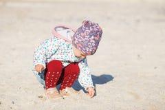 Śliczna mała dziewczynka bawić się na piaskowatej plaży Szczęśliwy dziecka być ubranym obraz stock