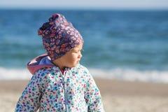 Śliczna mała dziewczynka bawić się na piaskowatej plaży Szczęśliwy dziecka być ubranym zdjęcie stock