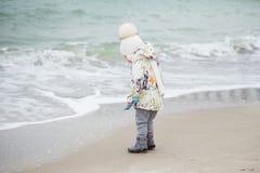 Śliczna mała dziewczynka bawić się na piaskowatej plaży Szczęśliwy dziecka być ubranym zdjęcie royalty free