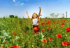 Śliczna mała dziewczynka bawić się w czerwonych maczkach odpowiada letniego dzień, piękno zdjęcia royalty free