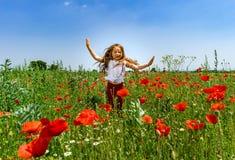 Śliczna mała dziewczynka bawić się w czerwonych maczkach odpowiada letniego dzień, piękno obraz royalty free