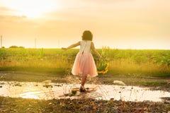 Śliczna mała dziewczynka bawić się w kałuży Obraz Royalty Free