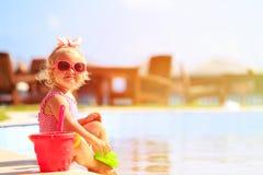 Śliczna mała dziewczynka bawić się w pływackim basenie przy plażą obrazy stock
