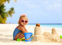 Śliczna mała dziewczynka bawić się z piaskiem na plaży Obraz Stock