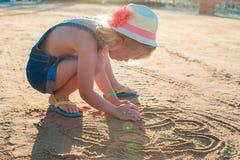 Śliczna mała dziewczynka bawić się z piaskiem na plaży Zdjęcia Royalty Free